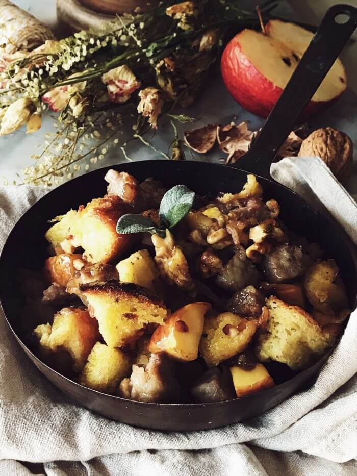 Italian sausage stuffing with apples, pandoro, walnuts, and olive oil in a pan