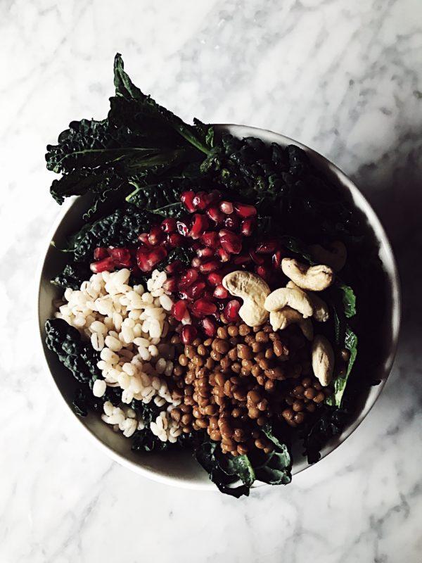 a raw kale Buddha bowl with lentils, barley, cashews and pomegranate vinaigrette
