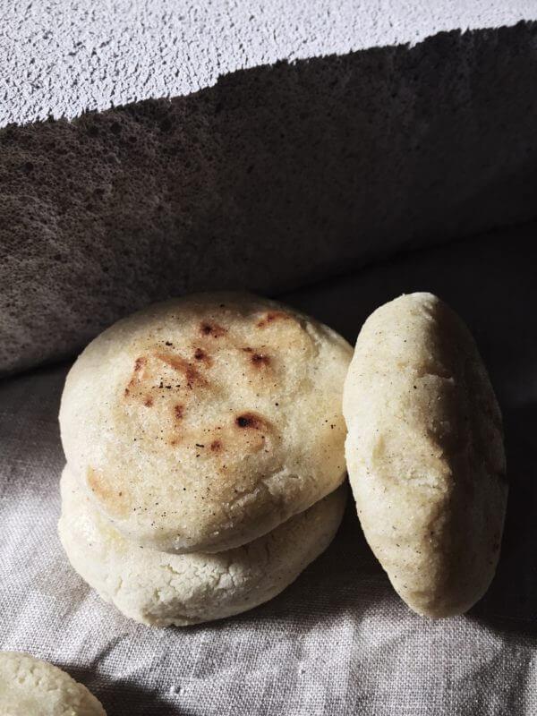 arepas recipe three patties on a grey backdrop