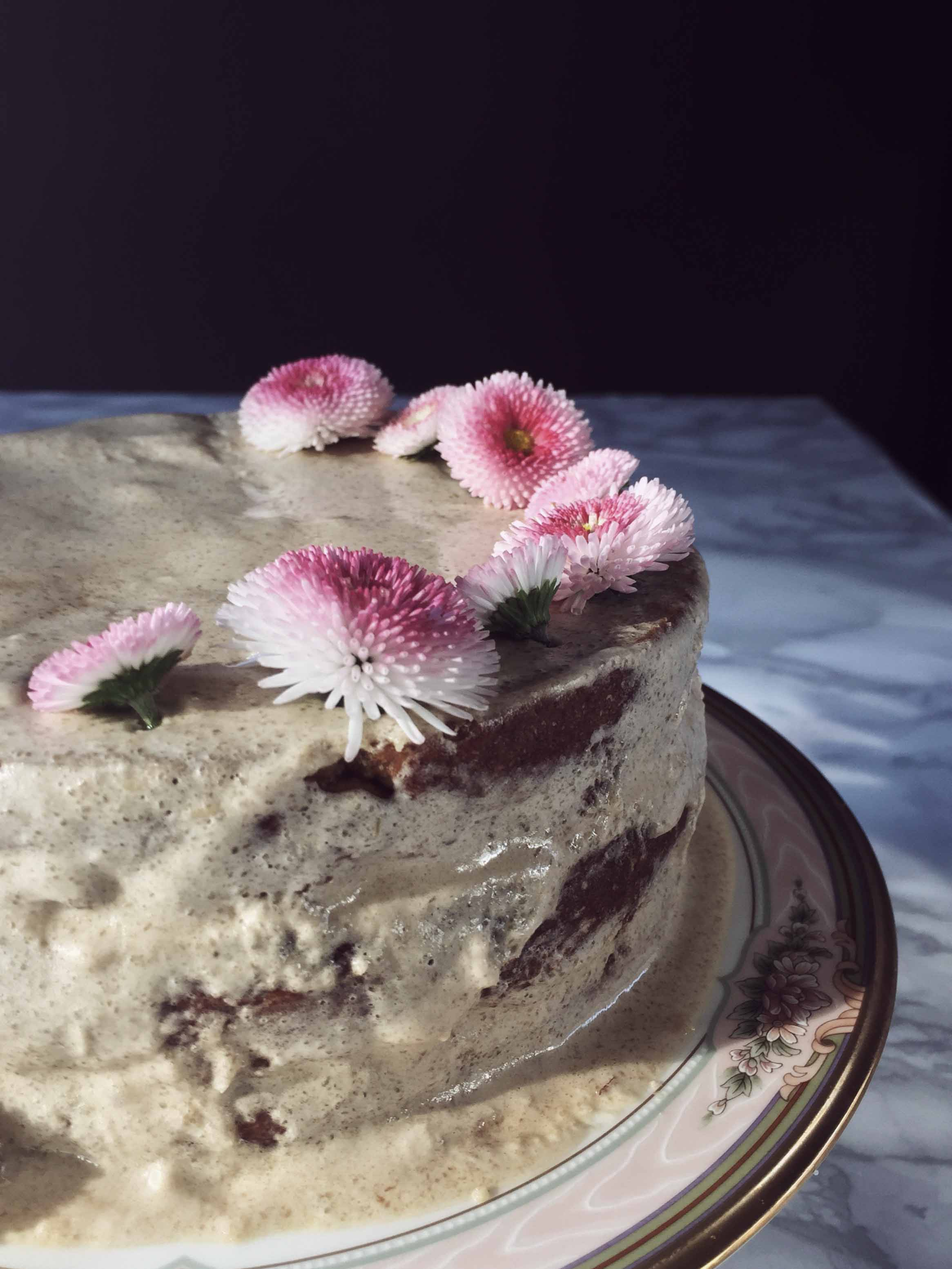 olive oil carrot cake with frosting and edible flowers