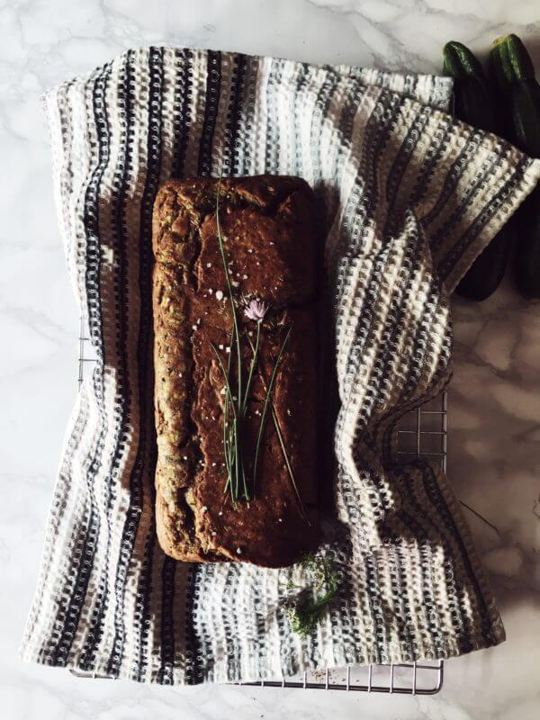 savory zucchini bread on a kitchen cloth with chives flowers