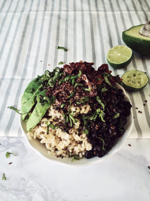 un buddha bowl vegetariano e caraibico: riso integrale, avocado, fagioli neri, coriandolo e semi di lino