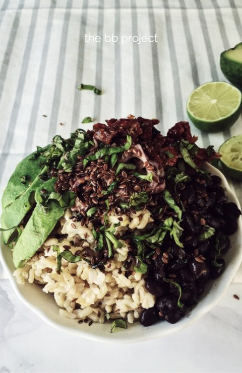 a caribbean and vegetarian buddha bowl: brown rice, avocado, black beans, cilantro & flax seeds