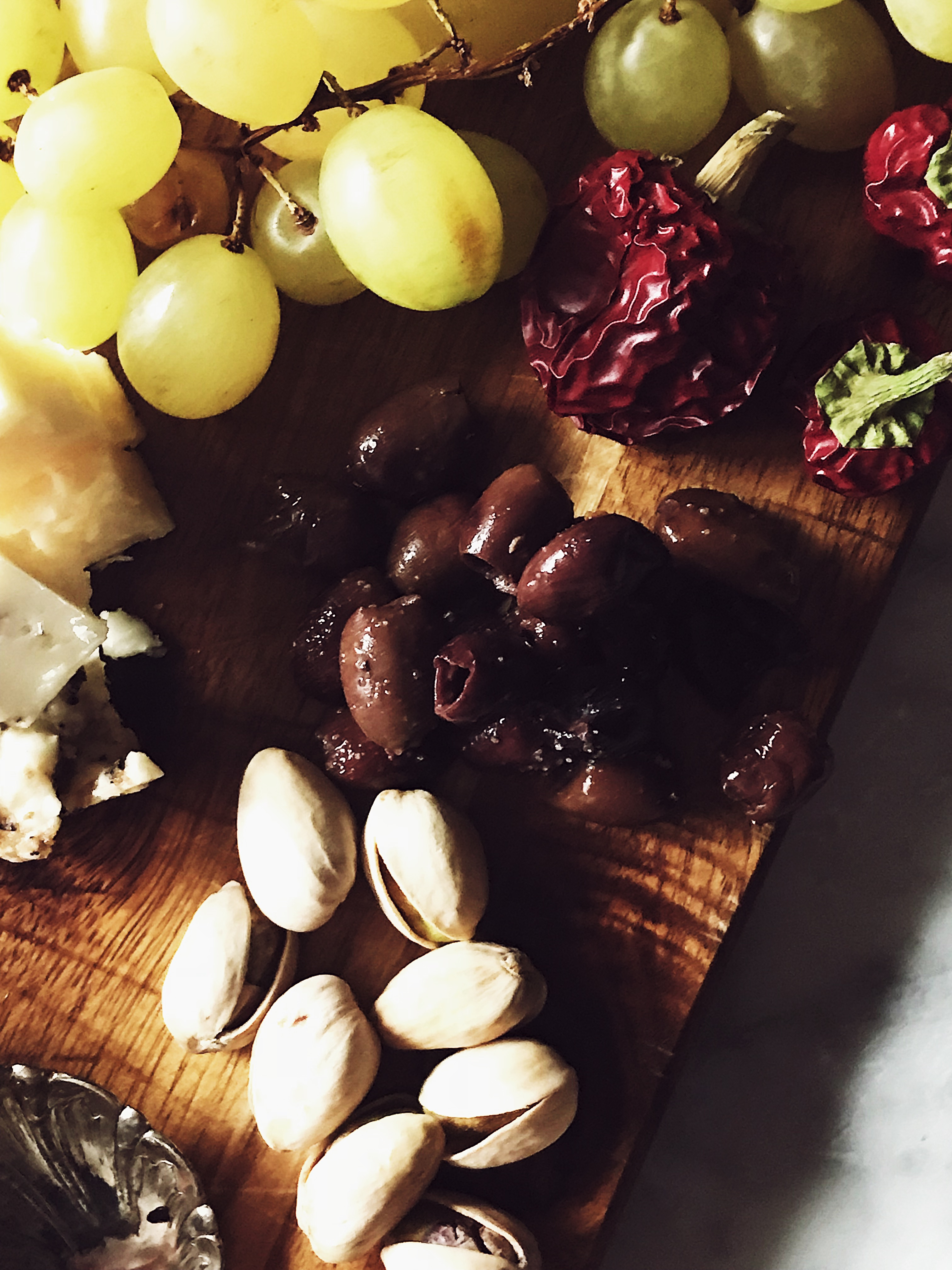cheeses, grapes, olives, and pistachios on a wood cheese board