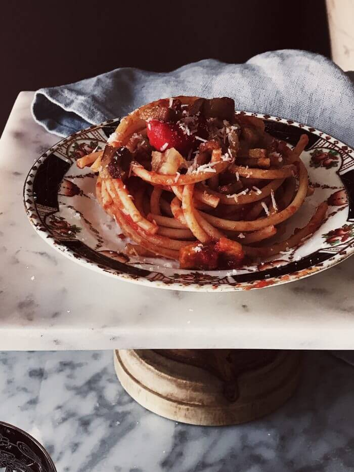 amatriciana pasta in a plate on a marble stand