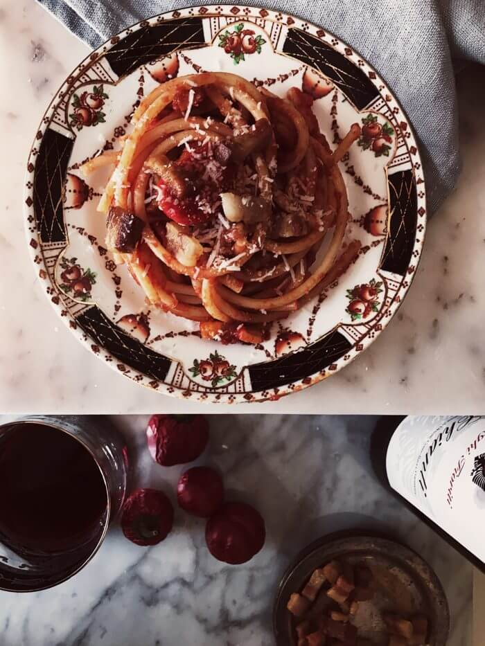 authentic amatriciana recipe on a fine china plate with a wine glass and bottle