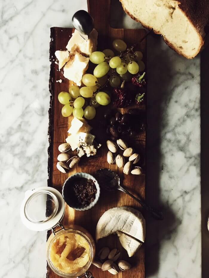 wooden cheese board with Italian cheeses, olives, pistachios, grapes, and Italian bread