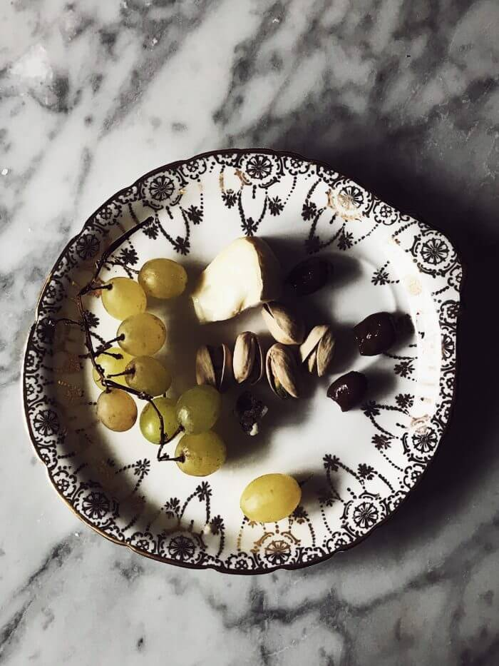 a slice of cheese, grapes and pistachios on a white and golden fine china plate