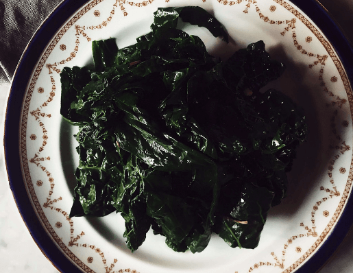 cooked kale on a white and blue vintage plate