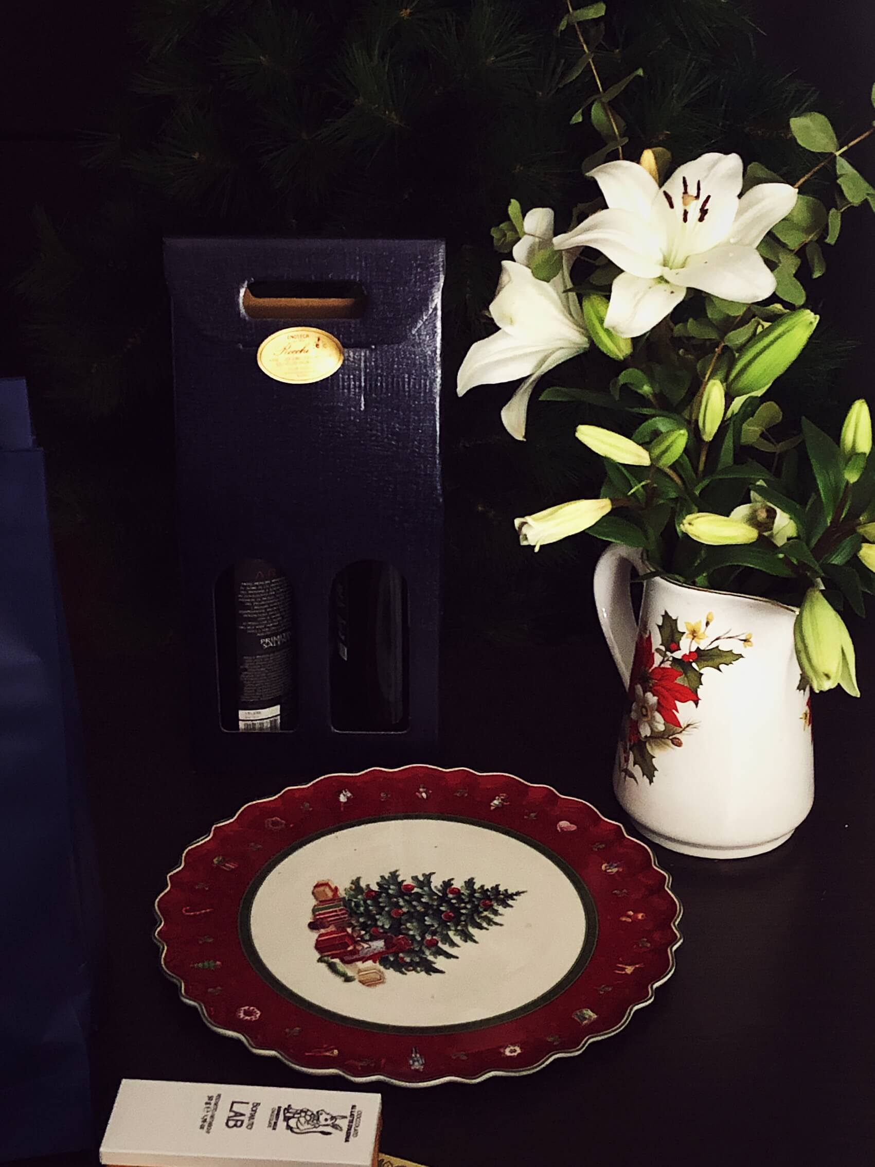 Christmas flowers, a plate, and two bottles of wine