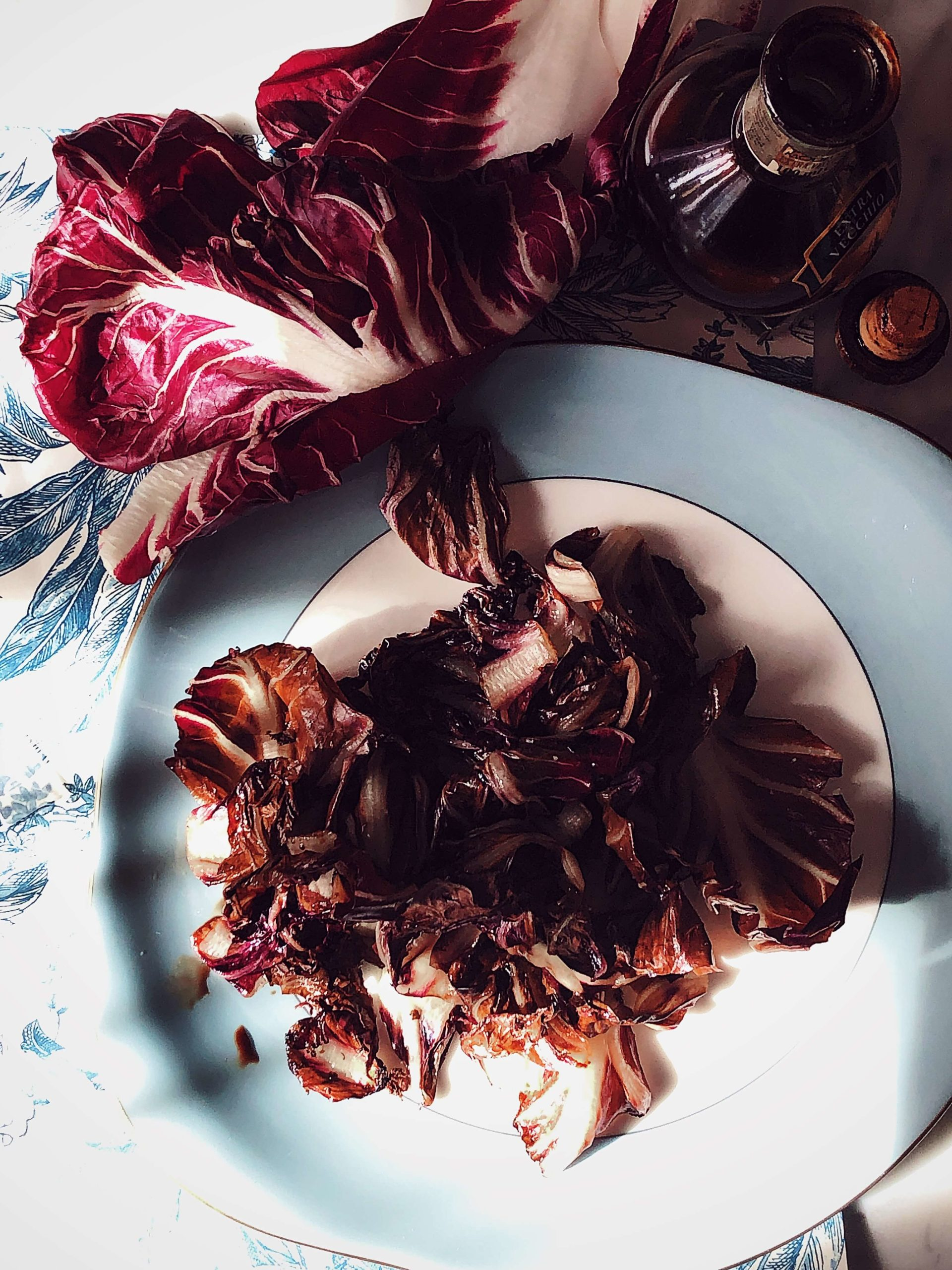 grilled radicchio with balsamic vinegar, raw leaves of radicchio, and a bottle of balsamic vinegar